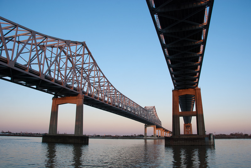 """<span id=""""title"""">Bridge at Sunset</span> <em>Crescent City Connection</em> Before I visited, I thought that maybe I could walk out on the bridge and get some photos. I quickly learned that would not be happening. It's cars-only and very high off the ground. It literally goes over the convention center before stretching out over the river."""