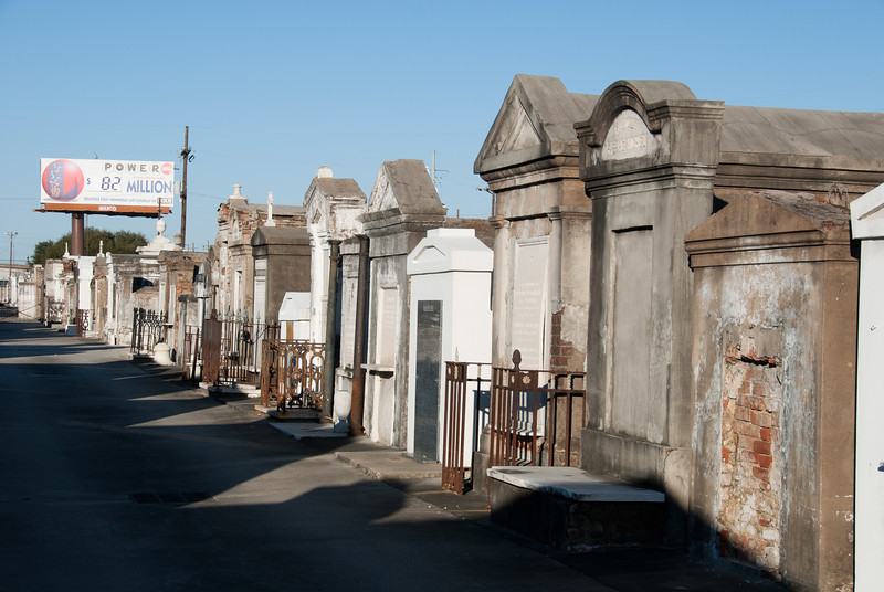 """<span id=""""title"""">PowerBall</span> <em>St. Louis Cemetery No. 2</em> Of course the  billboard is supposed to be seen by drivers on I-10, but it's still kind of funny. These folks were probably well-off to have tombs like these, but they're all dead now."""
