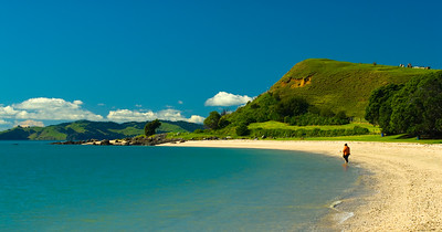 A woman enjoys the solitude of Maraetai Beach near Auckland New Zealand