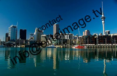 The buildings of Auckland city reflection on the still waters of viaduct harbour.