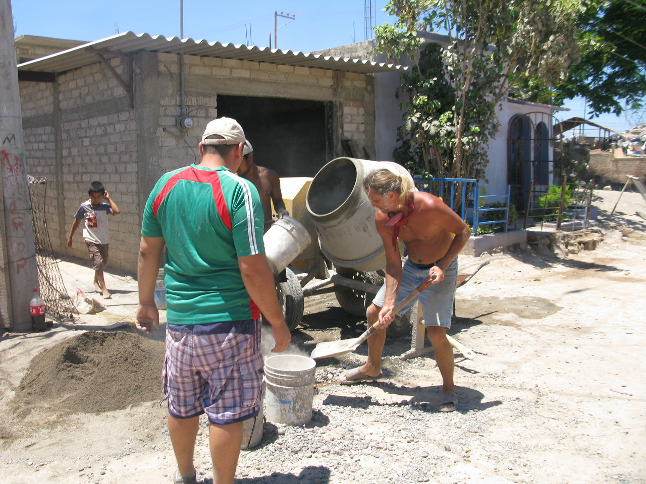 Despite the heat, the volunteer crew works on finishing another house.