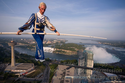 Jay Cochrane completes the first performance of Skywalk 2012, the Greatest Building to Building skywalk in North American history. Cochrane will grace the Niagara Falls skyline from the Skylon Tower (520 feet tall) to the top of the Hilton Hotel (581 feet tall) for the entire summer. At 1300 feet distance, he will cover approximately 20 miles on this wire in the 81 scheduled performances.  Photo by Skywalk2012.com  No Mags / No Sales / One Time Use Only with Permission  Jay Cochrane Skywalk2012 first day on July 6, 2012 from the Skylon Tower to the Hilton Fallsview Hotel, 1300 feet across in Niagara Falls, Canada.