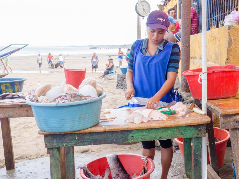 A young vendor prepares her goods for market.