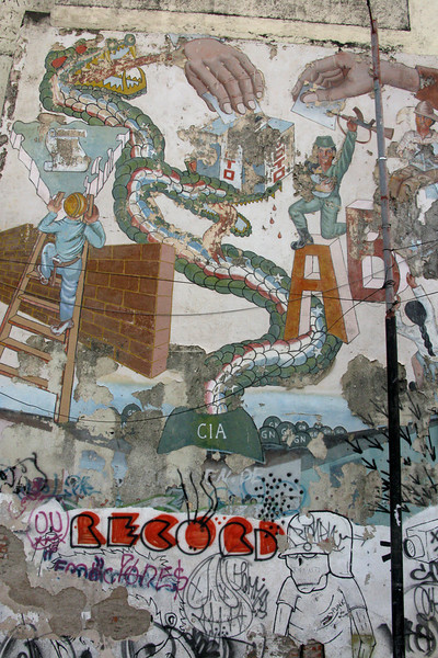 """Famous mural depicting the CIA as a snake biting a Nicaraguan hand at the ballot box, despite the Sandinistas' effforts at reconstruction and other projects following their takeover in 1979. In the early 1980s, under Reagan and his illegally armed Contras (which he called """"freedom fighters"""" and supported to counter the Sandinistas), the CIA was involved in several damaging attacks on the Nicaraguan economy and infrastructure."""