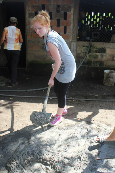 Laura schippt Beton für die Fundamente einer Anlage.