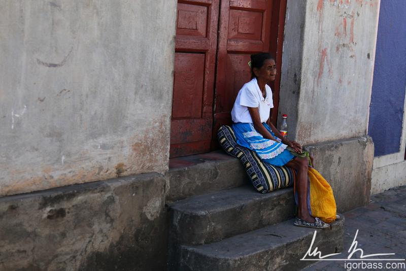 Elderly woman sitting on steps, Granada