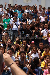 This is a group of school children on a field trip. The arm that you see on the bottom left of the frame belongs to the priest that was leading the group. He had the kids arrange themselves on the stairs and was taking their photo with a tiny little camera.  I stood on the bumper of a jeep behind him with my gigantic camera and the kids thought it was the funniest thing in the world! He didn't know I was behind him and bumped into me after taking his photo. I apologized, he said no problem and he lined the kids for me again and had them shout something in Spanish to me and wave. However, I like the photo with his arm in it the best! Granada, Nicaragua.