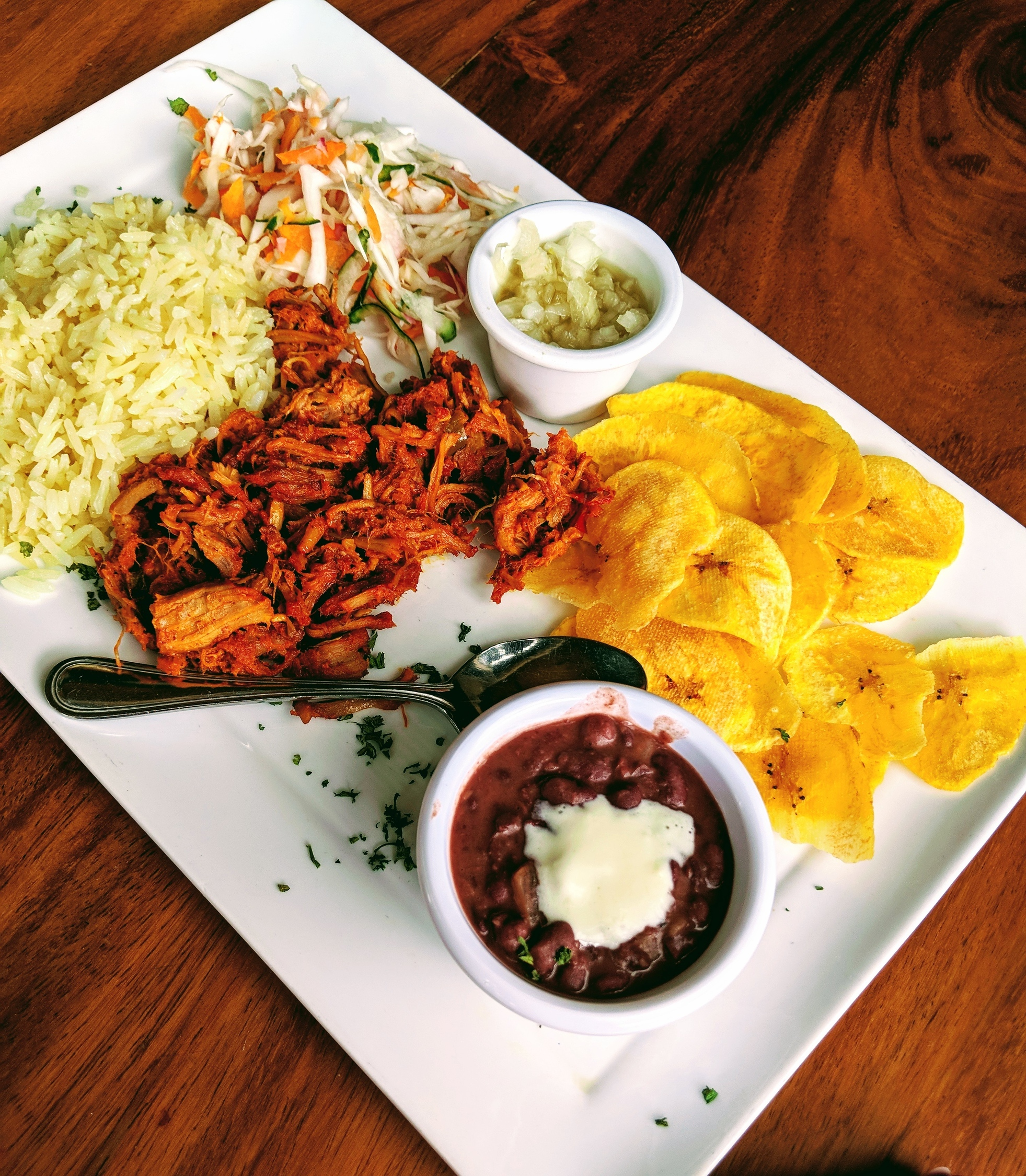 typical Nicaraguan food on a plate on a brown table.