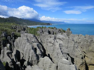 Typisch voor NZ. Blauwe lucht boven de oceaan, wolken boven land.