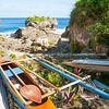 Paddle on top of outrigger canoe in gap between coral rock outcrops