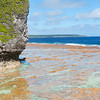 Red colored coral shelf surounding bottom of island of Niue