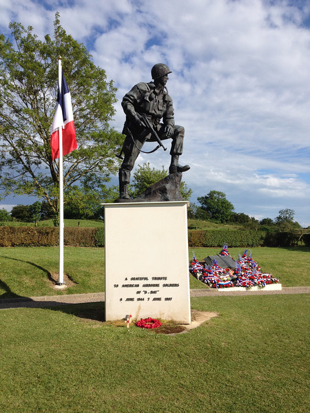 """La Fiere bridge memorial.<br /> <br /> A replica of the Fort Bragg """"The Airborne Trooper"""" stands above the bridge at La Fiere in Normandy, where on June 6–9, 1944 members of 505th Parachute Infantry Regiment and 325th Glider Infantry Regiment, both elements of the 82nd Airborne Division, fought a fierce battle against repeated German attacks. The small stone bridge over the Merderet River was a key point for the Germans to take in order to break up the American landing at Utah Beach, while at the same time being key to the Americans so that they could expand their beachhead in Normandy. Over the course of the battle, the Germans attacked the lightly armed Americans with both infantry and armor but were never able to cross the bridge."""