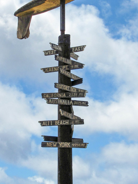 A sign topped with a surfboard points the direction to various locations around the globe from Oahu's North Shore.