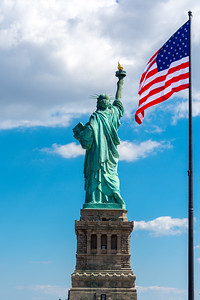 Statue of Liberty from behind with American flag