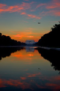 An plane flies over the Lincoln Memorial at dusk