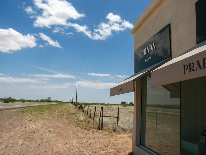"""Prada Marfa. From a plaque at the site: """"Established: October 1, 2005. Artists: Elmgreen & Dragset. Commissioners/Producers: Art Production Fund; Ballroom Marfa. Architects: Ronald Rael and Virginia San Fratello; Joerg Boettger. Construction: The Maxwell Company. Art Production Fund and Ballroom Marfa present PRADA MARFA, a site specific, permanent land art project by artists Elmgreen & Dragset. Modeled after a Prada boutique, the structure includes luxury goods from the fall 2005 collection. However, the sculpture will never function as a place of commerce, the door cannot be opened."""""""