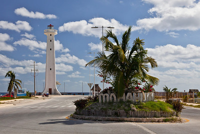 Mahahual, Mexico The boulevard leadng down to the village of Mahahual has a welcoming sign with a view of the lighthouse in the background. Mahahual is next to Costa Maya where the cruise ships dock.