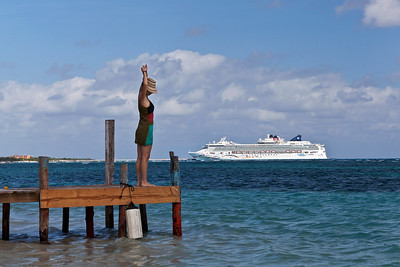 Mahahual, Mexico A woman stretches on the pier in Mahahual. In the background is a view of the Norwegian Star docked in Costa Maya.