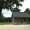 Kitchenhouse with Smokehouse in Background - Bennett Place Historic Site - Durham, NC<br /> This was also reconstructed from original materials from the Proctor farm site.  On many small farms and large plantations, the kitchen was separate from the main house due to frequent fires and the intense heat from the constant cooking.  The kitchen primarily provided an expanded workspace for preparing meals and performing other chores.  James, Nancy and Eliza retired to the kitchen when Johnston and Sherman arrived for their meetings.  Information on the Smokehouse is in a later photograph description.