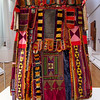 Egungun Masquerade Costume, circa 1930-1950 - North Carolina Museum of Art - Raleigh, NC   8/31/12<br /> Artist Unknown, Yoruba peoples, Ogbomosho region, Nigeria.  Cloth, wood and buttons.  The Yoruba peoples honor their ancestors during the annual and biennial egungun ceremony.  The tailor who fashioned this egungun costume appliqued its panels with motifs drawn from Yoruba, Islamic, and European traditions.  The wearer could see through the net face panel, adorned with wood and buttons.  The number of layers probably reflects the aage of the costume: each year the family that owned it added new layers of valuable cloth to honor their ancestor.  The earliest fabrics in this costume are French cotton voiles from the 1930s and the outer layers consist of fabrics produced in the 1950s.  When performing an acrobatic dance, the wearer would spin rapidly so the fabric panels flew out, revealing the colorful layers of the costume.