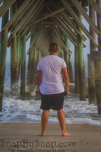 A Man on the Beach with a Pier