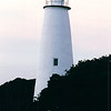 Ocracoke Lighthouse - Ocracoke, NC  10-27-98<br /> Ocracoke Lighthouse's modest height (75 feet), subdued color scheme (solid white), and tranquil setting (a small island on the east side of Ocracoke Inlet) belie the dramatic history of its surrounding area. The calm waterway that today carries pleasure boats and small fishing craft witnessed its share of treachery, heroism, and adventure long before the lighthouse stood sentinel over the inlet.  Ocracoke hardly had an auspicious beginning; it was put on the map after an English sailing ship was wrecked on the shoal-ridden inlet in 1585. But its eventual useful role as a waterway access to various inland ports pales in comparison to the high drama played out in its waters. True, the gifted and dashing Sir Walter Raleigh landed on Ocracoke at least once during his explorations of the new world, but the real excitement came from another reckless Englishman—Edward Teach, better knows as Blackbeard, the most ruthless and dreaded of pirates.  By 1718, Blackbeard had come to regard Ocracoke as his favorite anchorage.