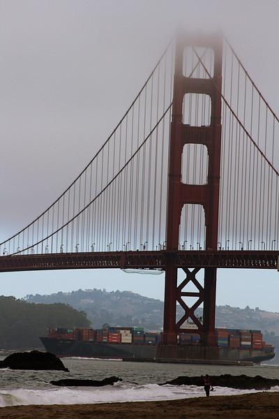 Notice the container ship passing beneath the bridge.