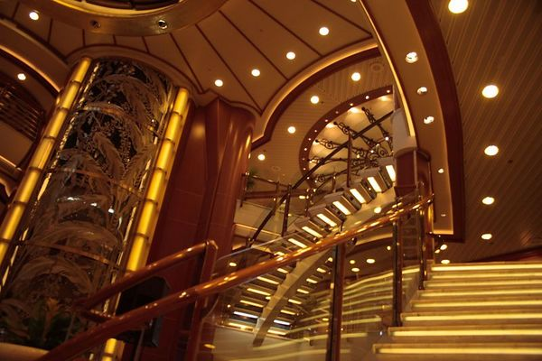 The main lobby on a cruise ship is always a dramatic sight. Here you can see the elevator and the marble stairs. Boutiques line the area around the top floor.