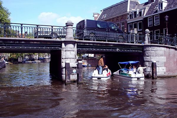 The pedal boats squeeze under the bridge.