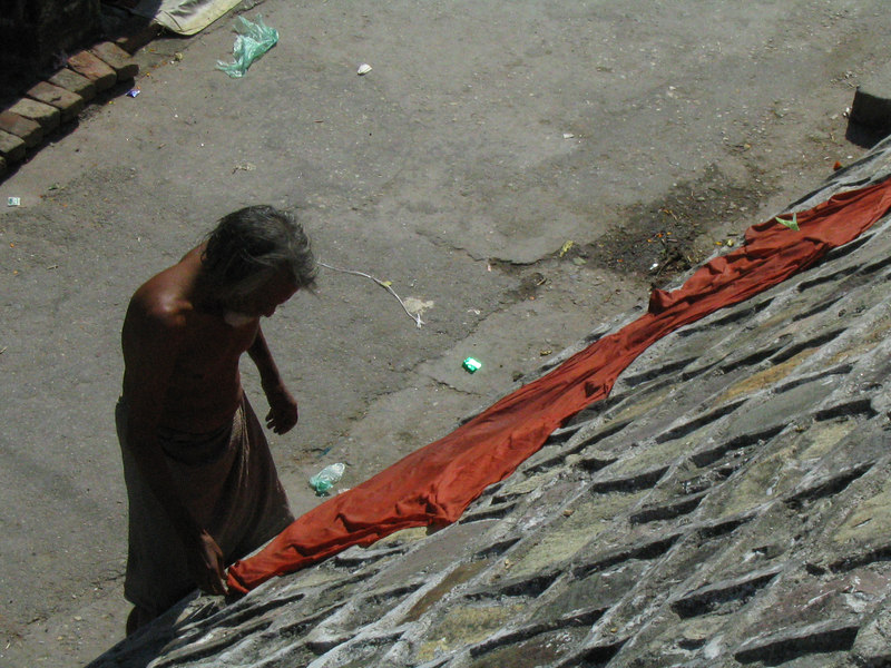 A sadhu drying his longyi.