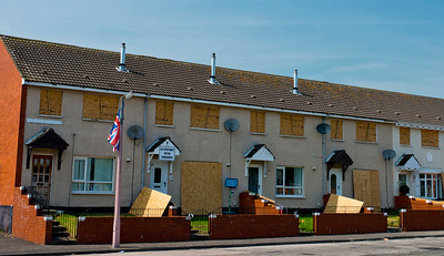 Houses facing the protestant bonfire on Hopewell Square in loyalist Belfast, are boarded up to protect against the heat.