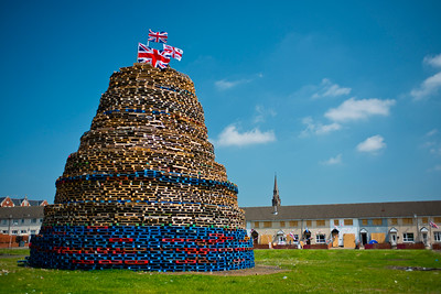 Protestant bonfire in Hopewell Square, part of the loyalist Shankill area of West Belfast. The houses in the background are boarded up to protect against the heat.