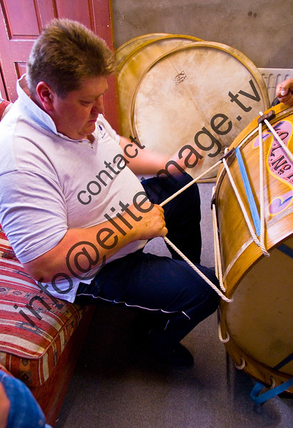 Stretching the goat skin head on a traditional lambeg drum in Northern Ireland. The Lambegs are different from other large drums in the quality of their tone. The thin heads are pulled tighter and tighter until the tone is bright and hard. There are no mechanical screws on the drums. The heads are held on with a wooden rim and linen ropes. (2)
