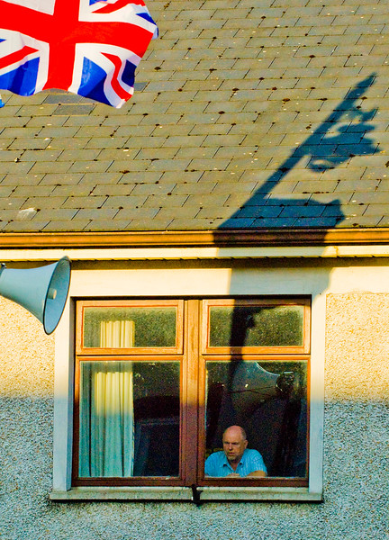 A man sits in the shadow of a union jack and the blare of the speaker - watching the annual loyalist band parade in Market Hill County Armagh Northern Ireland