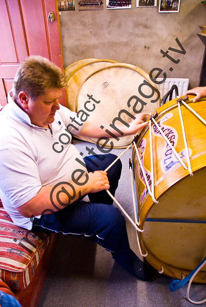 Stretching the goat skin head on a traditional lambeg drum in Northern Ireland. The Lambegs are different from other large drums in the quality of their tone. The thin heads are pulled tighter and tighter until the tone is bright and hard. There are no mechanical screws on the drums. The heads are held on with a wooden rim and, traditionally, linen ropes.