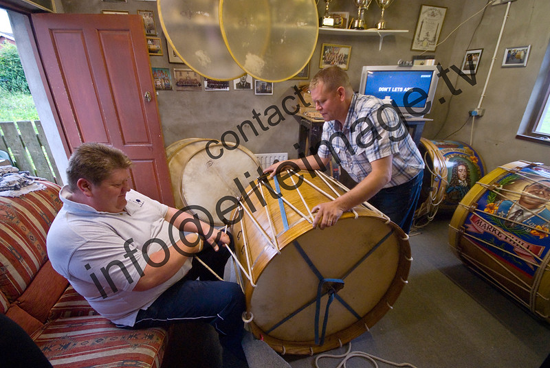 Stretching the goat skin head on a traditional lambeg drum in Northern Ireland. The Lambegs are different from other large drums in the quality of their tone. The thin heads are pulled tighter and tighter until the tone is bright and hard. There are no mechanical screws on the drums. The heads are held on with a wooden rim and linen ropes. (3)