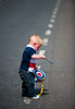 A young child plays with a unionist drum before the annual 12th of July Orange Order march through Waringstown, County Down, Northern Ireland