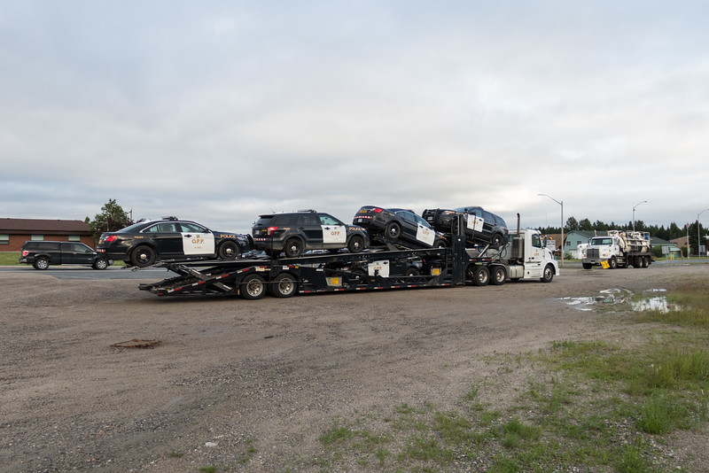 Ontario Provincial Police truck with trailer load of polilce vehicles in Cochrane.