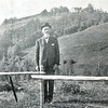 Lars A. Rossing, shown here with the family farm in the background, was 61 years old when he visited in 1906.