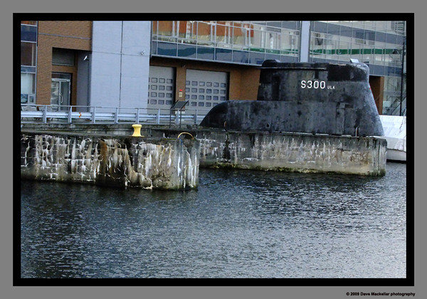 This is DORA: <br /> A German U-Boat submarine base and bunker built in 1941 to house 13 submarines in the Trondheim harbour. The black con tower by the entrance, labelled S300 is what remains of ULA S300, a British built Norwegian sub. She sank a German U-boat during one of her 14 missions off the coast of Norway during the Nazi attack on Norway and remained in Norwegian Naval service until 1965 when she was scrapped.