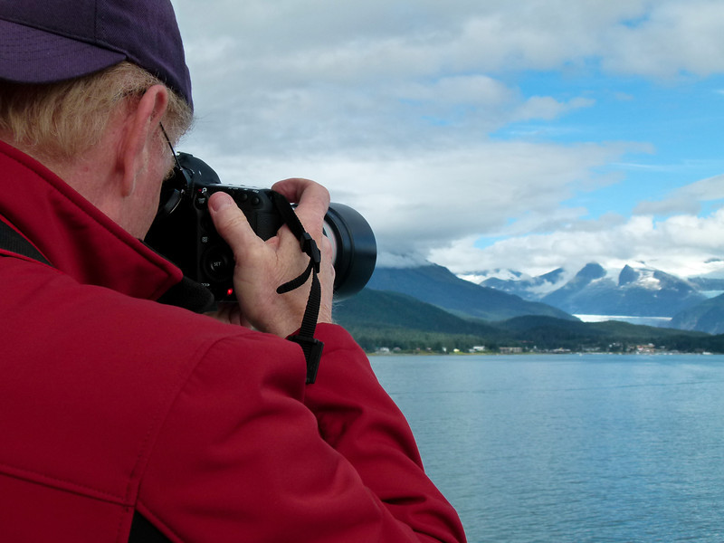 Man in a red coat taking a photo of a glacier