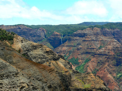 Red mountains topped by green jungle are part of the scene at Waimea Canyon on Kauai.
