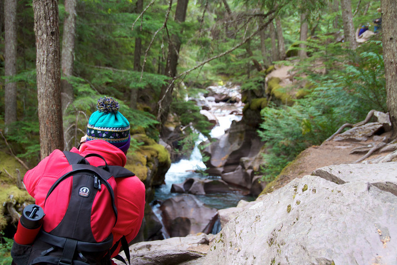 A woman stops to photograph water rushing along Avalanche Creek in Glacier National Park.