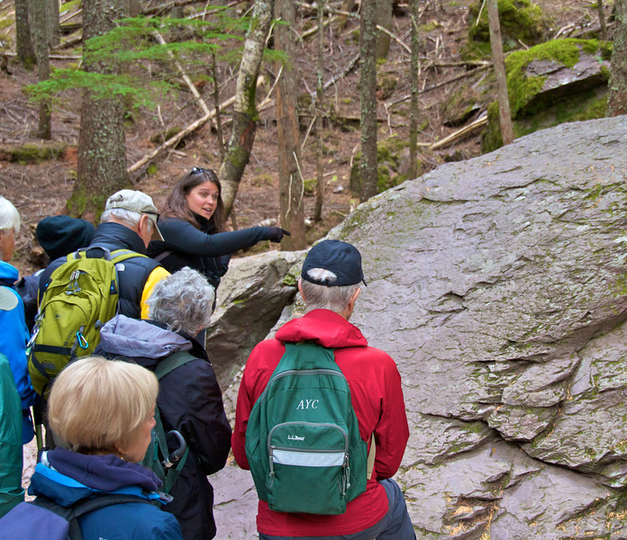 A teacher points out a geology feature on the trail.