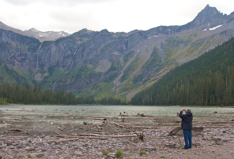A man holds up a camera to photograph Avalanche Lake.