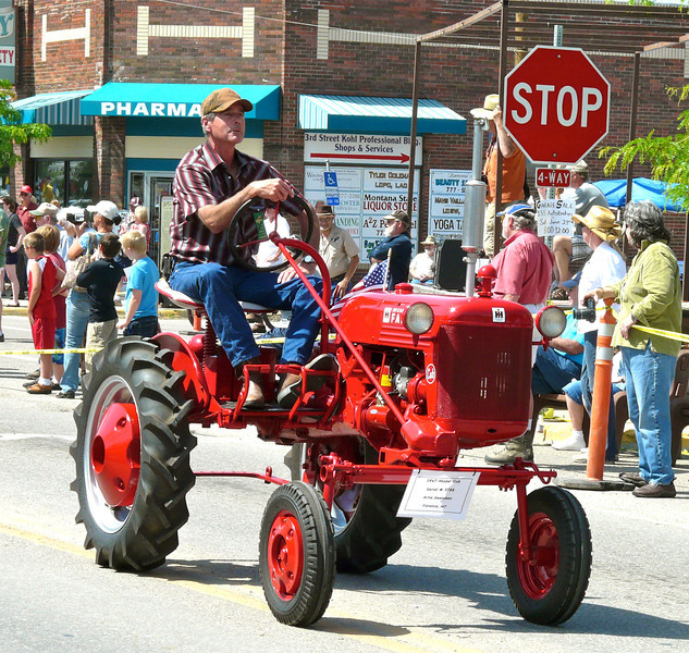 Antique tractor rolls down the street at the Western Heritage Days parade