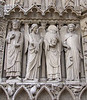 St. Denis holding his head.  At front exterior of Notre Dame