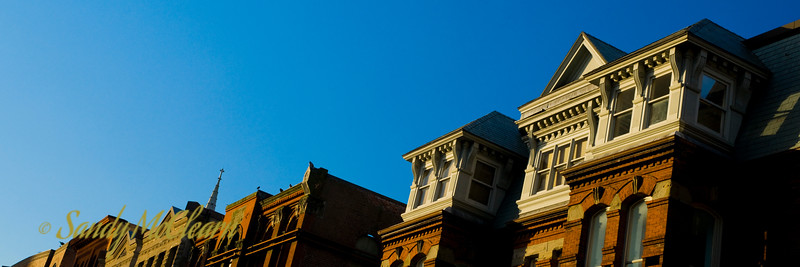 Dawn light hits the top of some buildings along a stretch of Barrington Street in this panorama.
