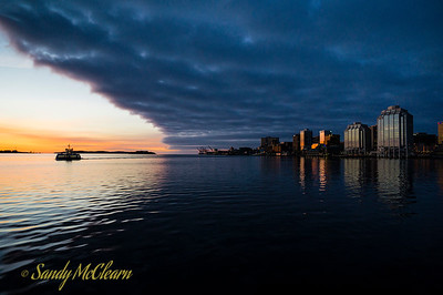 A curious combination of dawn versus dusk over Halifax Harbour, with the soon-to-rise sun reflecting off the buildings of the Halifax skyline before the cloud bank can completely shadow them.