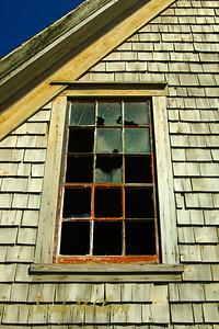 A broken window on a fishing shack.